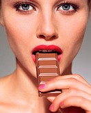 Woman eating bar of chocolate