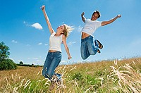 Couple jumping in a field