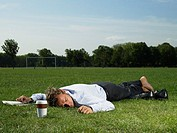 Male office worker sleeping in a park