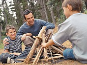Father and sons building a campfire
