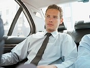 Businessman riding in back seat of car