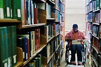 Male college student in wheelchair at library (thumbnail)
