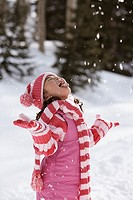 Girl catching snowflakes with tongue