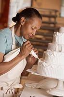 Side view of woman decorating cake