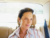 Woman sitting in back seat of a car, looking out window