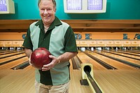 Man holding bowling ball at bowling alley (thumbnail)