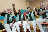 Men cheering at bowling alley (thumbnail)