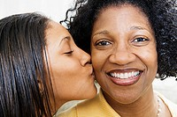 Close up of daughter kissing mother