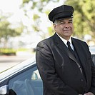 Portrait of chauffeur standing by car