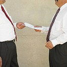 Midsection of businessmen holding papers