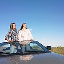 Two women standing in convertible