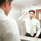 Businessman combing hair in mirror