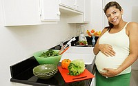 Pregnant woman in kitchen touching abdomen