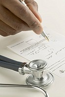 Close up of doctor's hand writing prescription