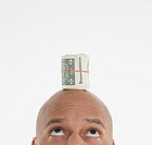 Man with roll of dollar bills on head