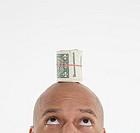 Man with roll of dollar bills on head