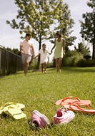 Family running in park with shoes off