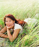 Young woman laying in sea grass
