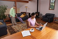 Woman working on laptop while man vacuums