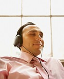 Businessman relaxing while listening to headphones