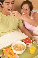 Young woman feeding boyfriend breakfast in bed