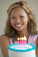 Young woman holding birthday cake