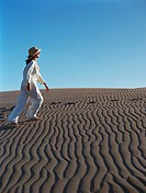Young woman walking barefoot on sand