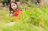 A girl holds a flower while sitting in a field