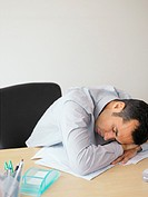 Young man sleeping at his desk