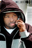 Young black man with cap and logo, cell phone