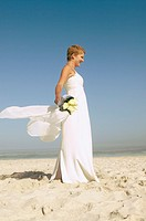 Bride standing on sandy beach