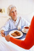 Elderly woman receiving breakfast in bed