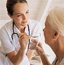 A nurse offers medicine to a patient