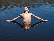 Man stretching arms in water