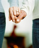 Couple holding hands and an engagement ring