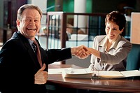 Businesswoman and a businessman shaking hands