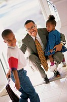 Businessman meeting his son and daughter at the door