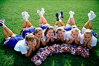 High angle view of cheerleaders lying on a lawn