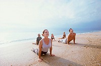 Group of people exercising on the beach