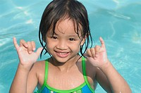 Thailand, Nong Bai Lumphu, Five year old Asian girl in pool gives the shaka sign.