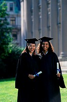 Portrait of two female graduates holding diplomas