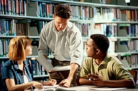 Two young men and a young woman discussing in a library