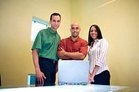 Low angle view of two businessmen and a businesswoman standing in front of a laptop