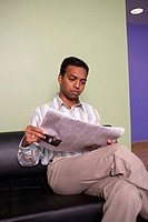 Businessman sitting on a couch reading a newspaper in an office