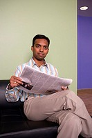 Portrait of a businessman sitting on a couch reading a newspaper in an office