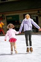 Rear view of two girls ice skating