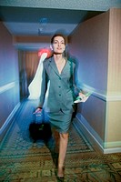 Businesswoman walking in a corridor with a suitcase