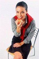 Portrait of a young woman sitting on a chair eating an apple smiling