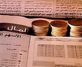 Piles of UAE coins on Arabic newspaper