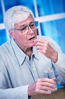 Senior man taking a pill